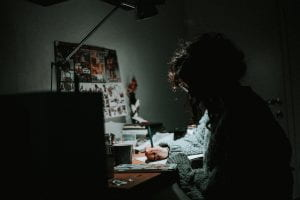 A person working at their desk at night.