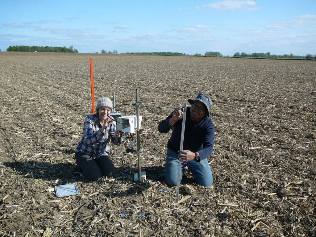 Two people in the field setting up flux measurement equipment