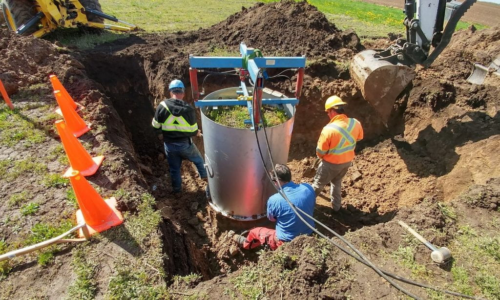 Three men stand next to filled steel cylinder in ground with surrounding soil removed