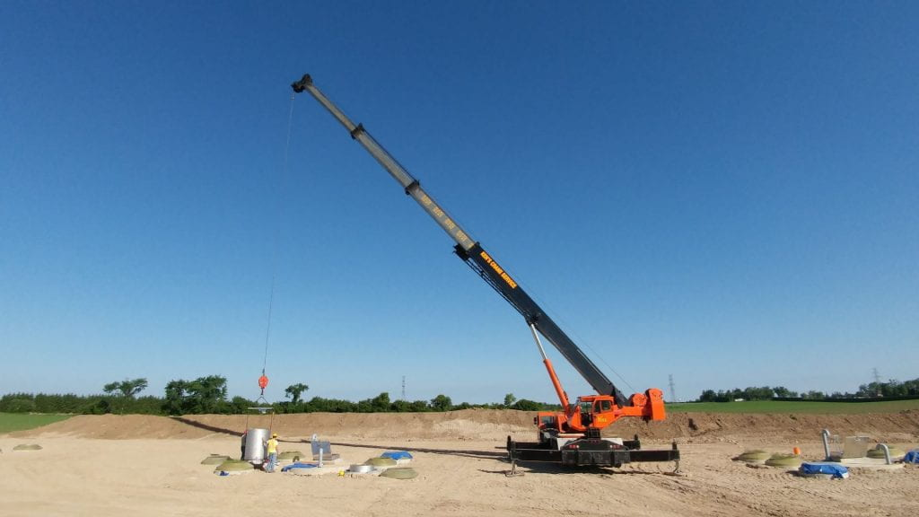 Large crane carrying soil core in an agricultural field