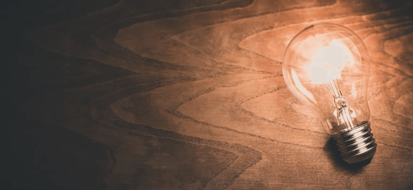 Lit lightbulb on a wooden background