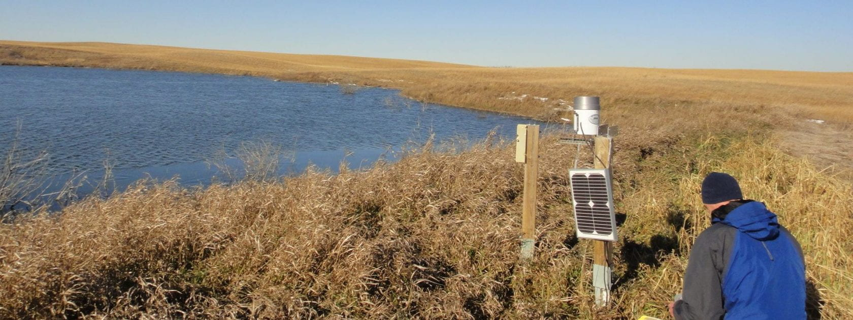 Aaron Berg in a field by a lake taking measurements with soil moisture equipment.