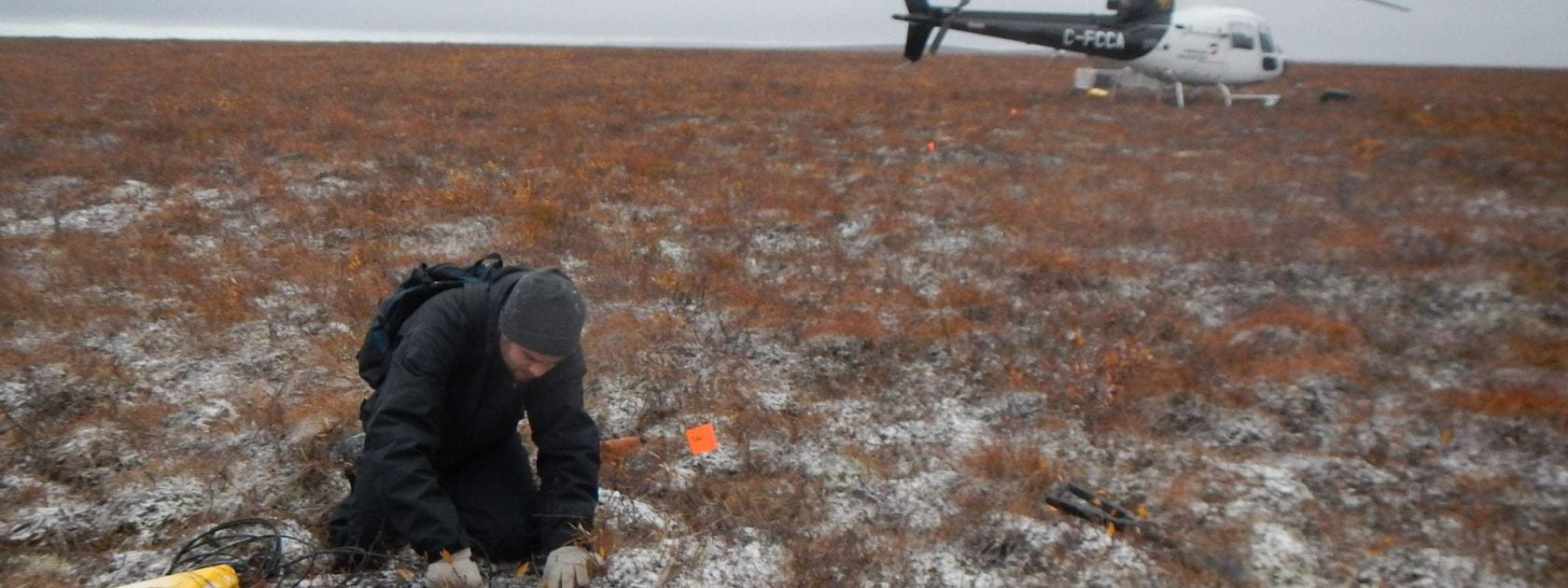 Grad student in arctic fieldwith helicopter in the background
