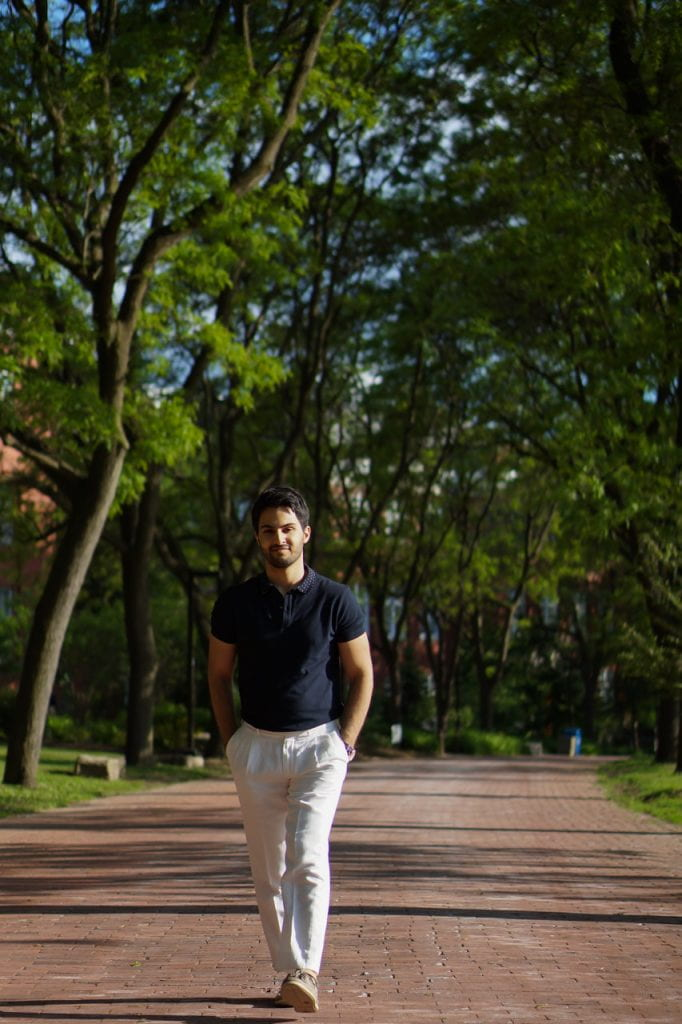 Image of Rene Sahba Shahmohamadloo walking along a brick path with trees.