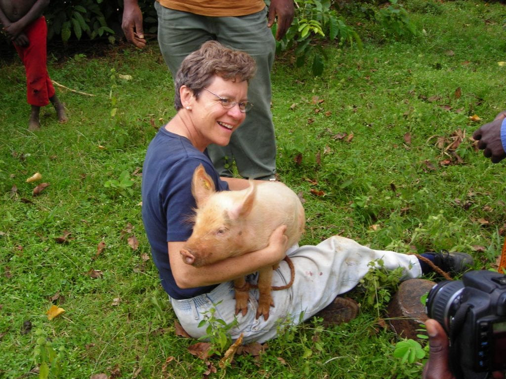 Image of Cate Dewey in Kenya sitting in the grass while holding a pig.