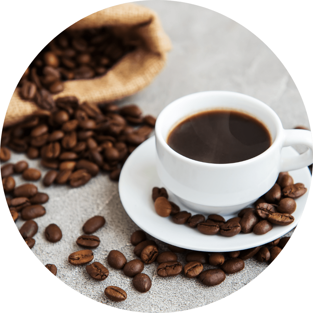 Image of a coffee cup with coffee in it surrounded by coffee beans.
