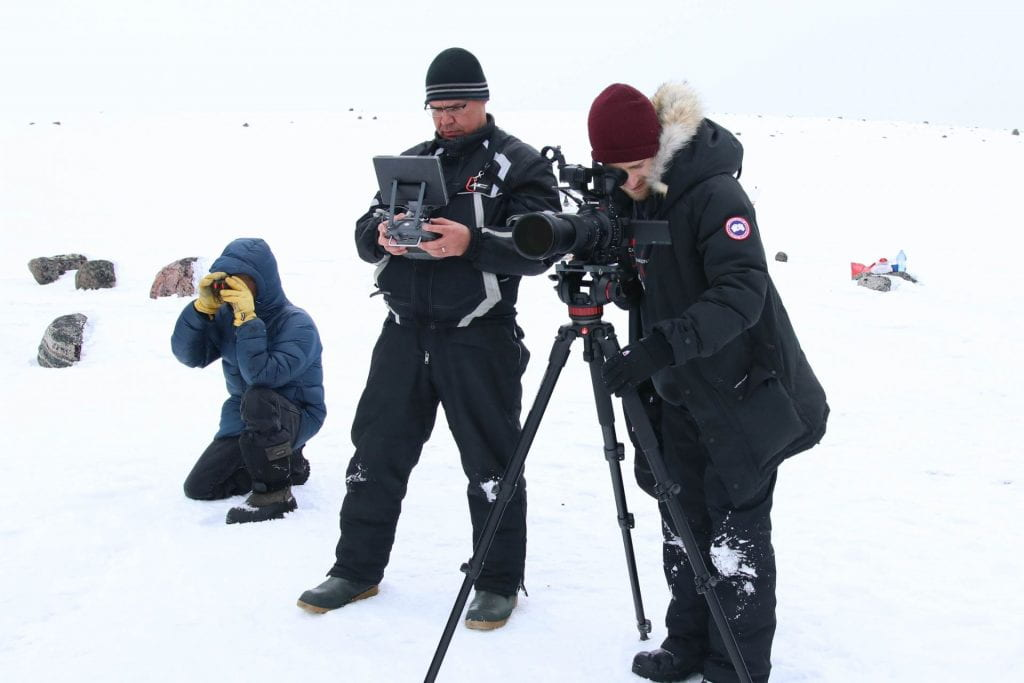 A photo of Henry Lyall from Nain, Eldred Allen from Rigolet, and David Borish standing beside one another holding equipment filming caribou in Labrador.