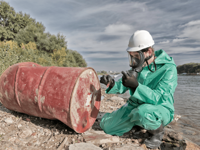 Image or worker inn green hazard suit and mask inspecting a barrel along the lake side.