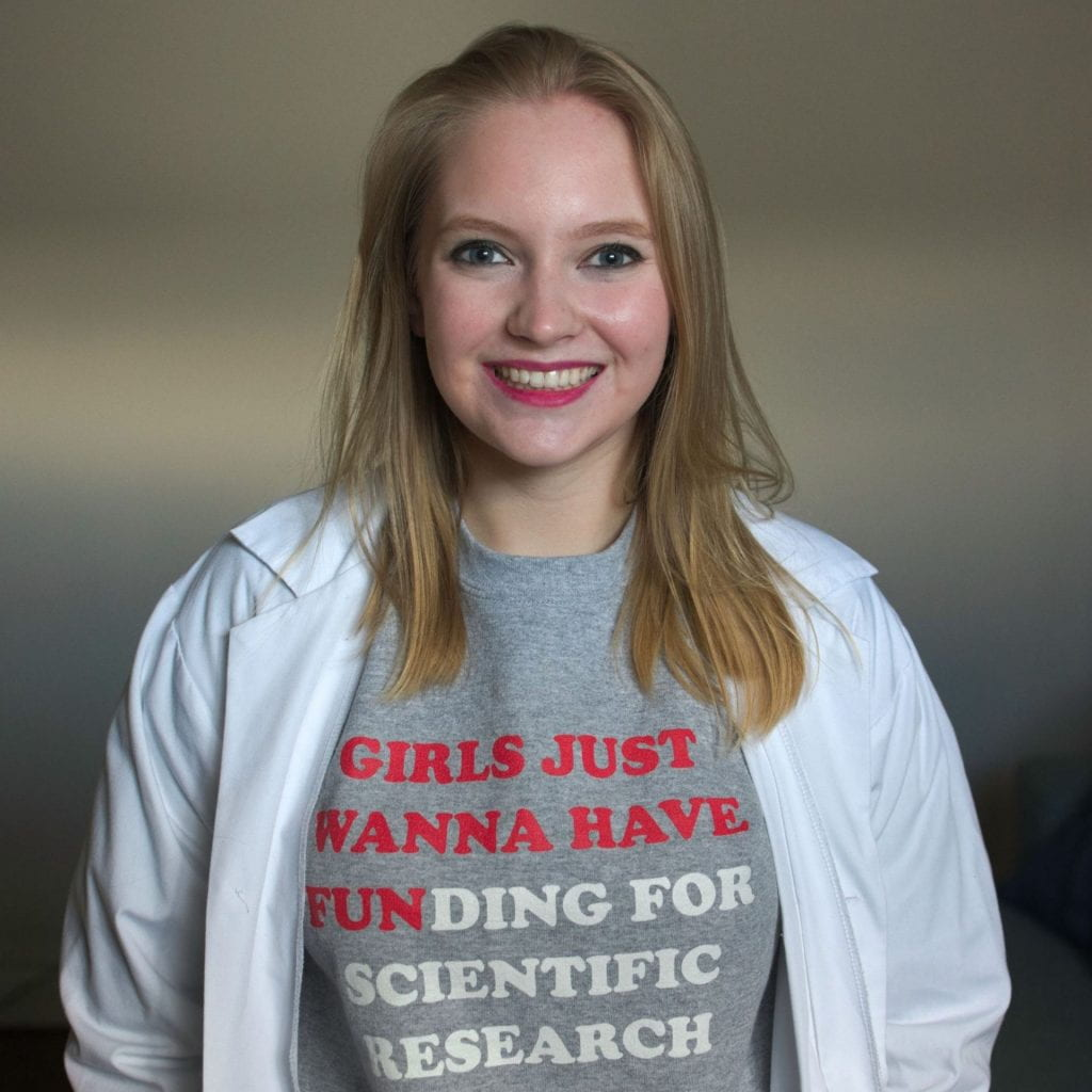 """Headshot of Nikola May wearing a shirt that says """"Girls just wanna have funding for scientific research"""""""