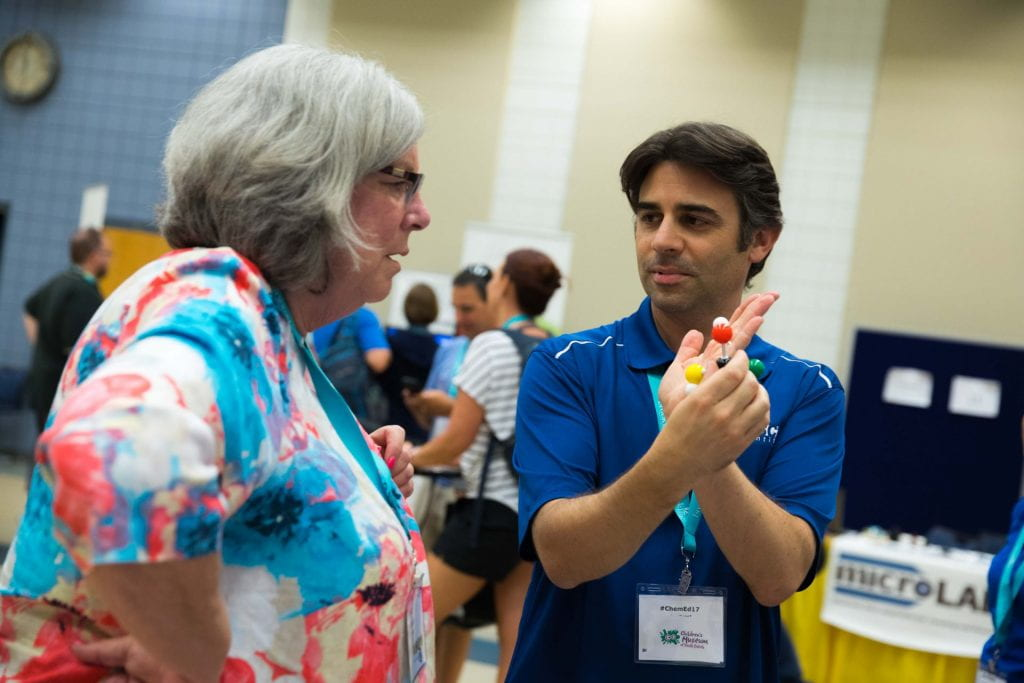 a man in a blue shirt holding a molecular model explaining something to a women in an exhibit hall