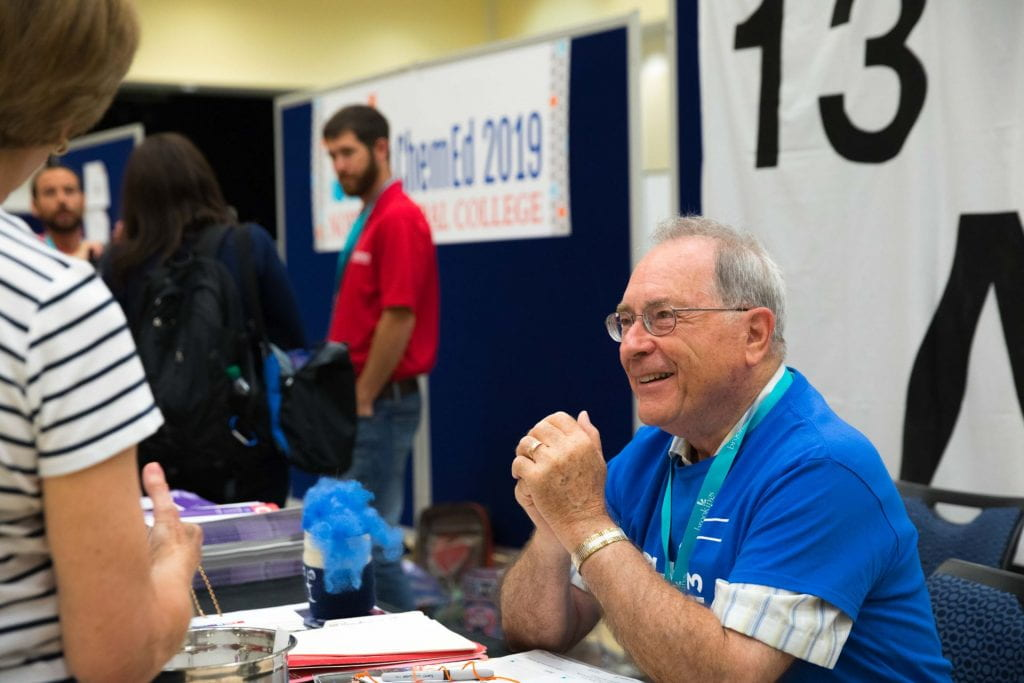 Lee Brubacher sitting at a exhibit hall table smiling and talking to people
