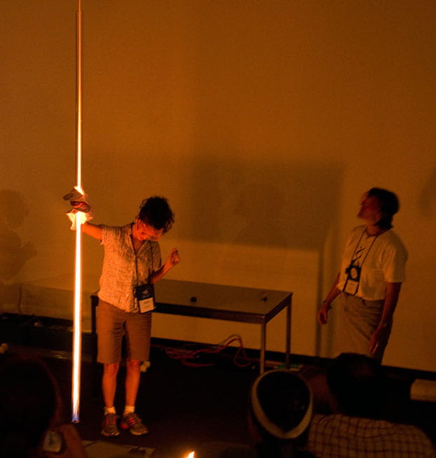 a darkened room with two women -- one holding a long glowing tube