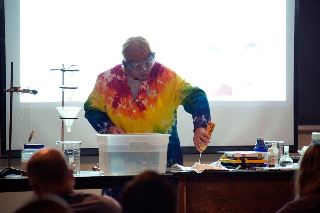 a presenter in a rainbow lab coat with a spray bottle