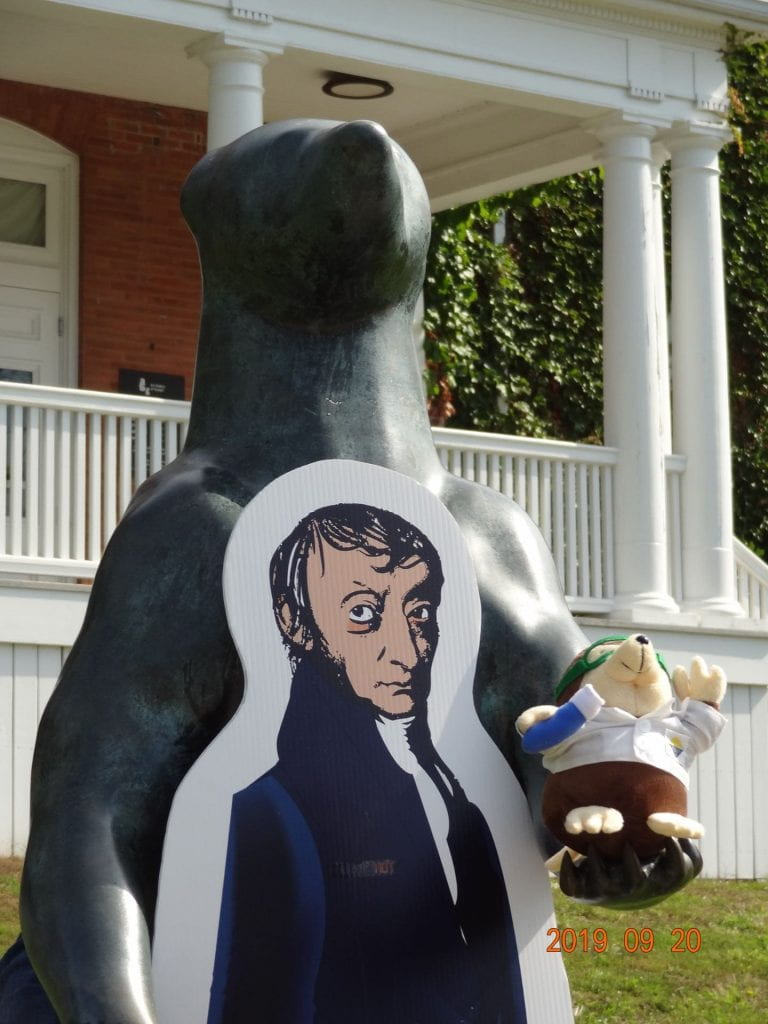 a statue of a standing bear holding a mole with a life-size Avogadro cutout