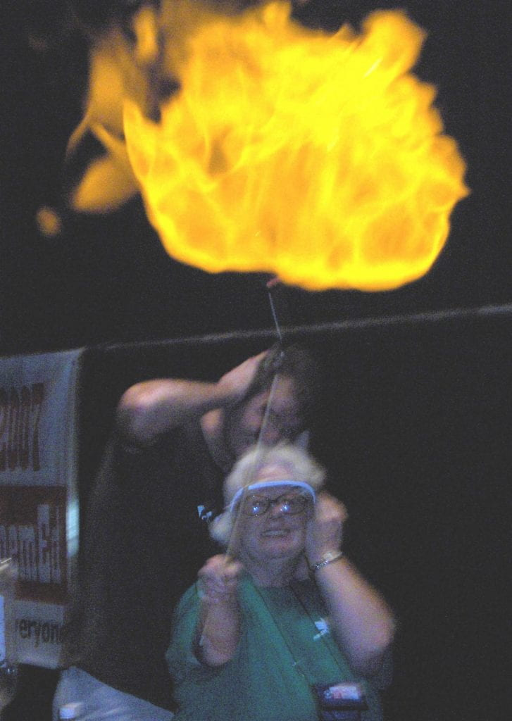 A large flaming ball with two people in goggles holding their ears
