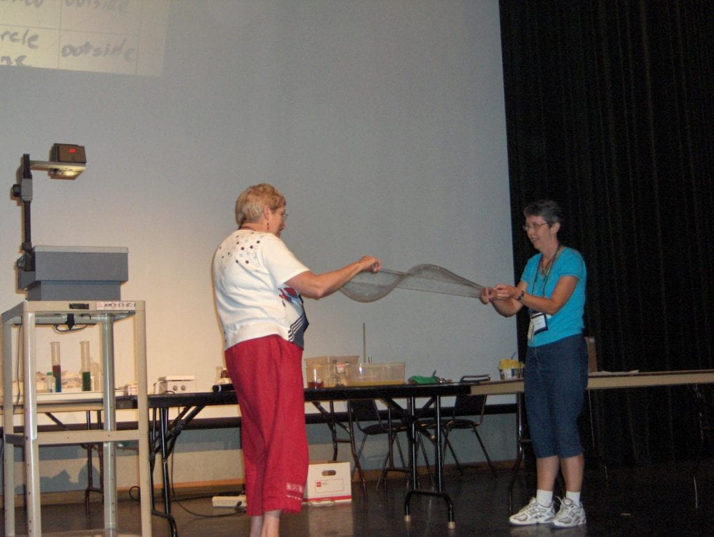 Two women holding string creating a bubble wave