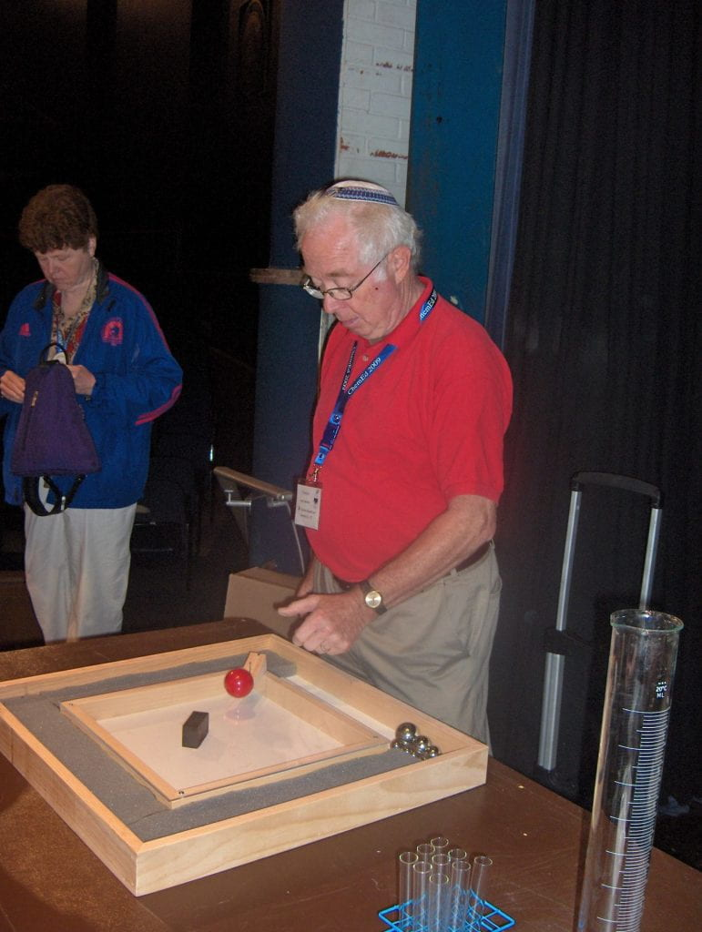 Irwin Talesnick with a wooden square board with two different coloured balls