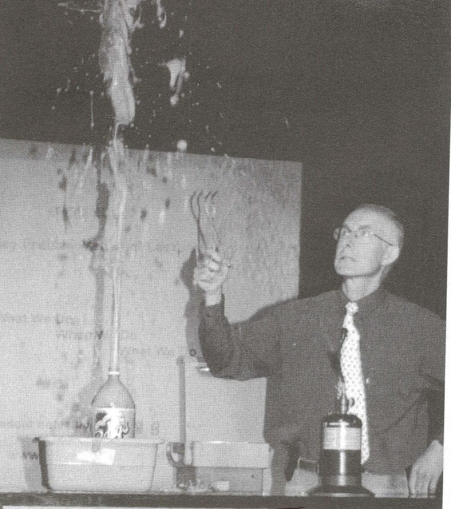 Doug De La Matter with a large soda pop bottle that is spraying foam upwards