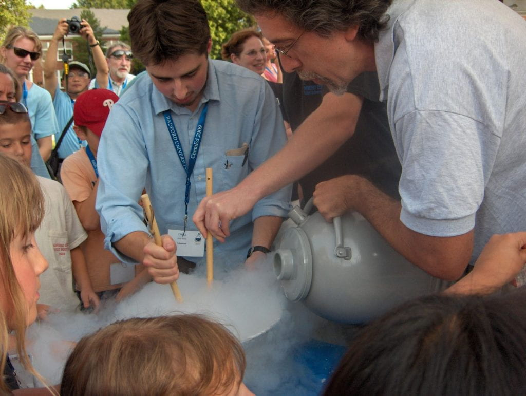 Outside picnic with someone pouring a dewar of liquid nitrogen into a stainless steel bowl to make ice cream