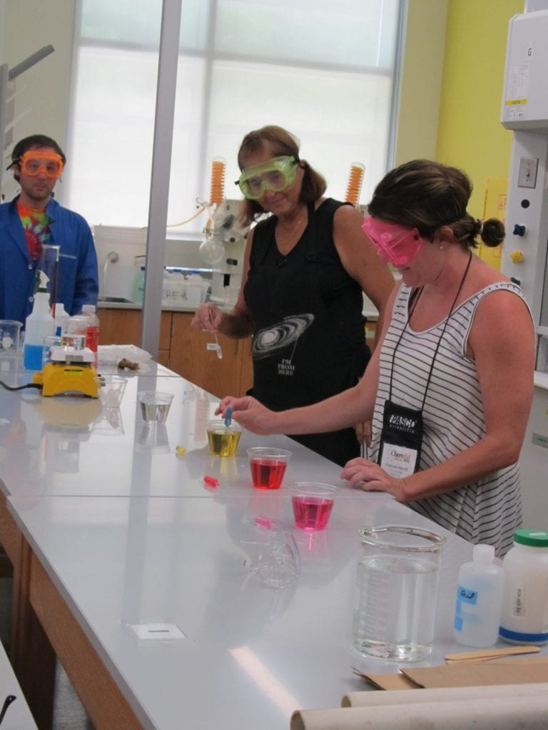Peggy Sconzo in a lab setting with several plastic glasses holding colourful solutions instructing a workshop attendee with an eye dropper