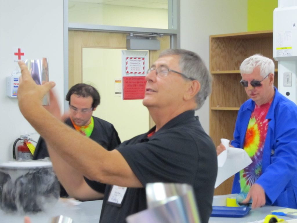 Pat Funk holding up a mirrored paper in a lab setting with ChemEd attendees in the background