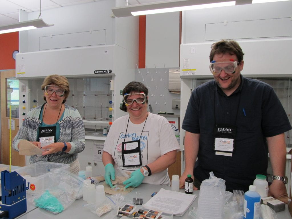 Three teachers with gloves on and equipment in a lab workshop