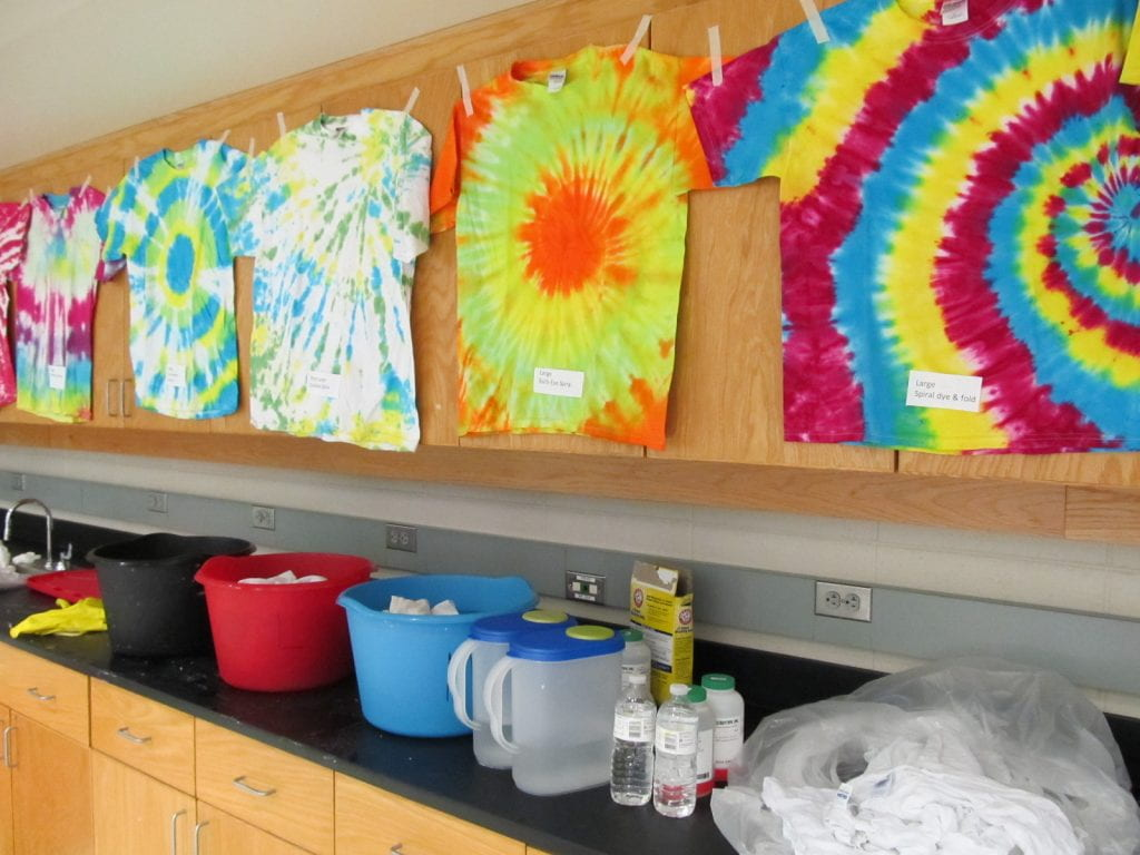 a lab with various colourful tie dyed T-shirts hung up along with buckets on the counters