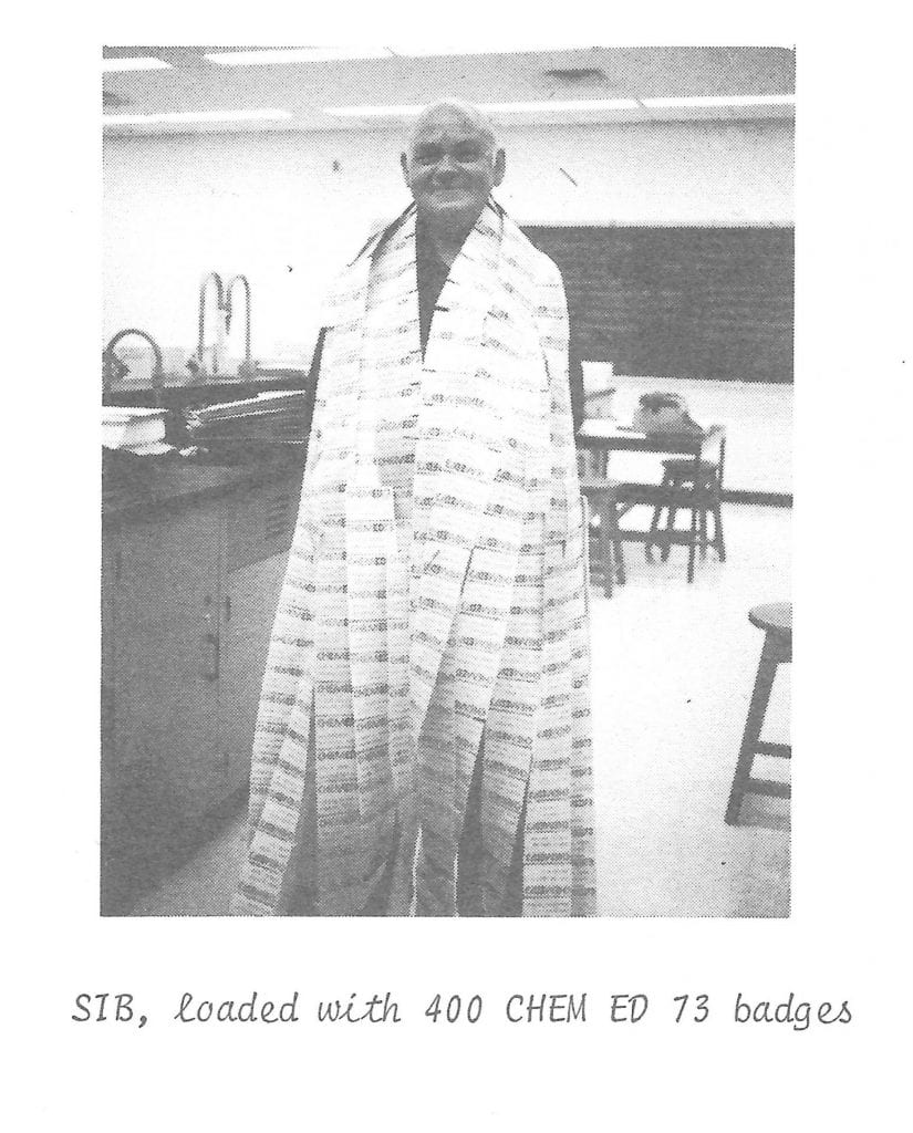Leonard Sibley in a black and white photo using strips of conference badges as a cape