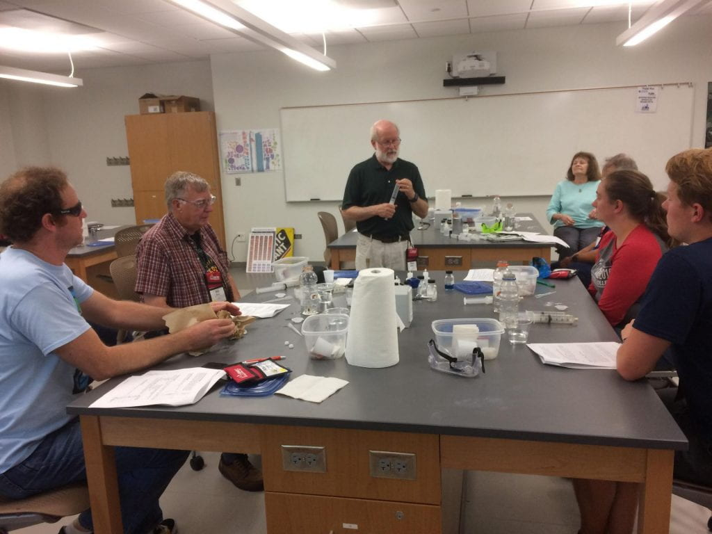 Bill Mattson explaining a demo while holding a syringe in front of a lab room full of attendees