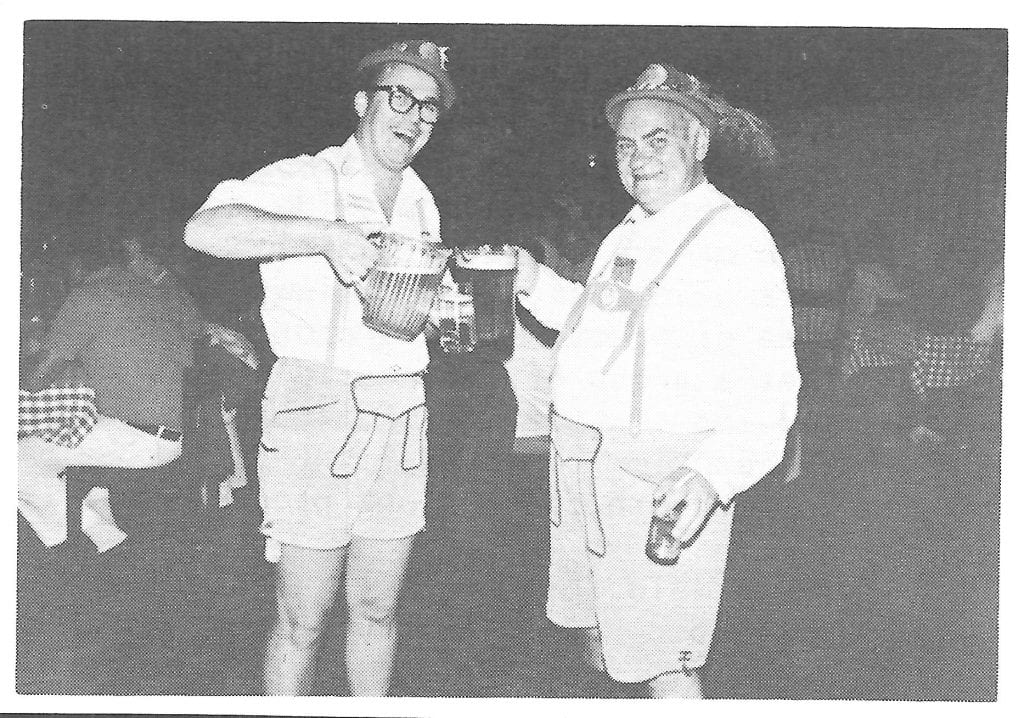 Reg Friesen and Leonard Sibley holding two large pitchers of beer at Oktoberfest