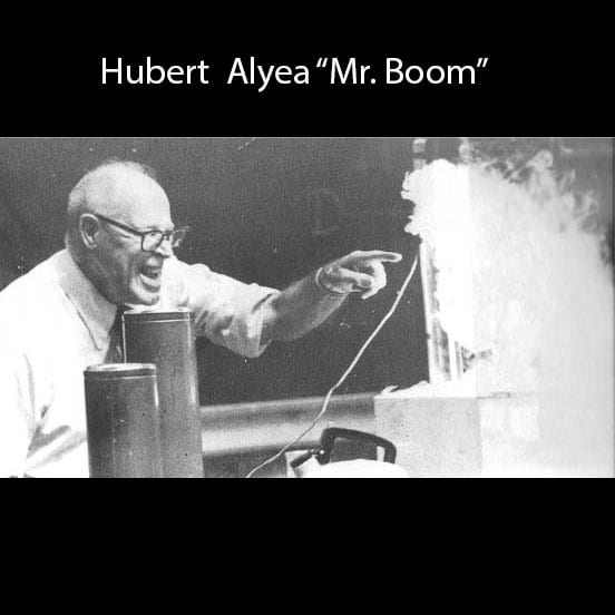 Hubert Alyea smiling and pointing at a smokey demonstration