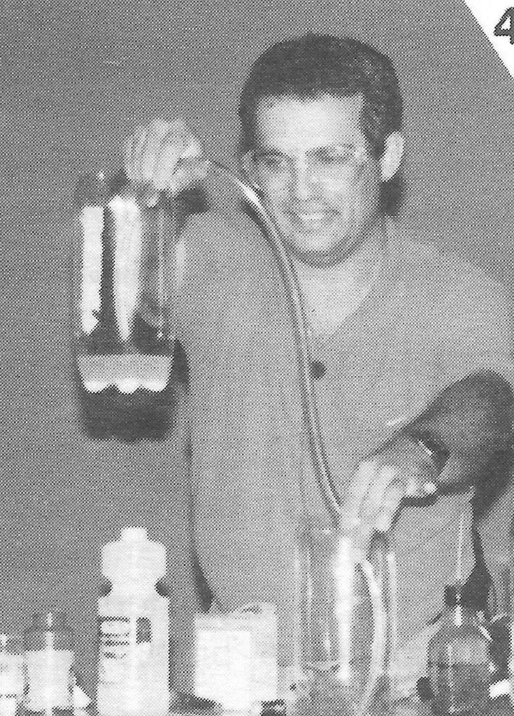 Bob Becker holding a tube between two large pop bottles filled with water