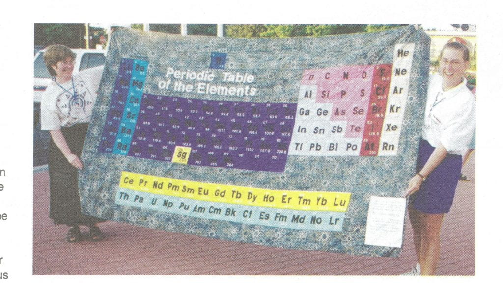 Two women holding a colourful periodic table quilt