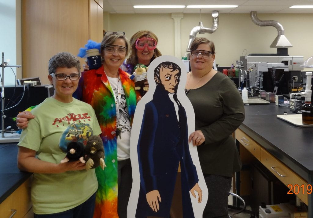 life-size cut out of Avogadro with Charlene Winchcombe-Forhan, Bonnie Lasby, Jean Hein and Kate Stuttaford in a lab settingice setting