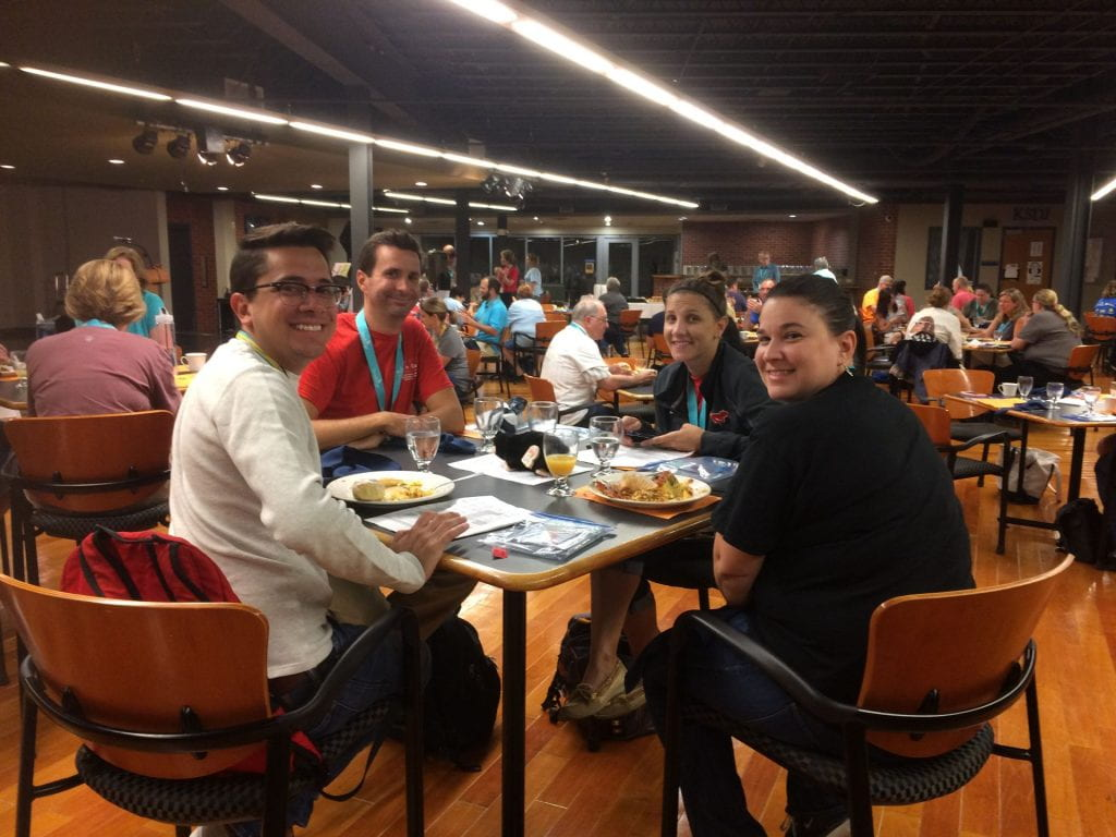a group of attendees sitting around a table with breakfast food all smiling