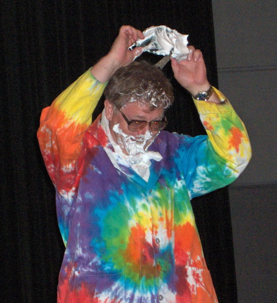 Andy Cherkas in a colourful tie dyed labcoat is pulling off goggles covered with white pie cream showing his eye are has been protected