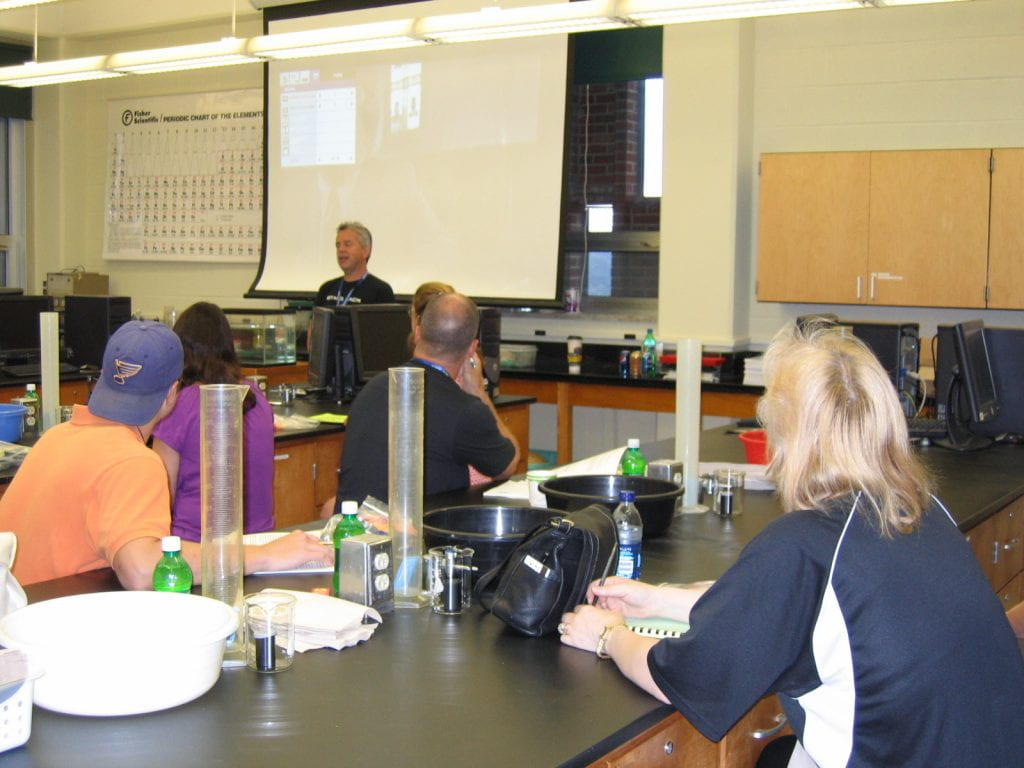 Brian Rohrig in front of a room full of attendees surrounded by high school lab equipment