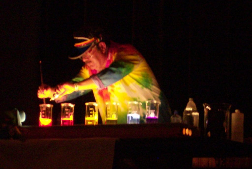John Fortman presenting a demonstration a darkened room with colourful glowing beakers