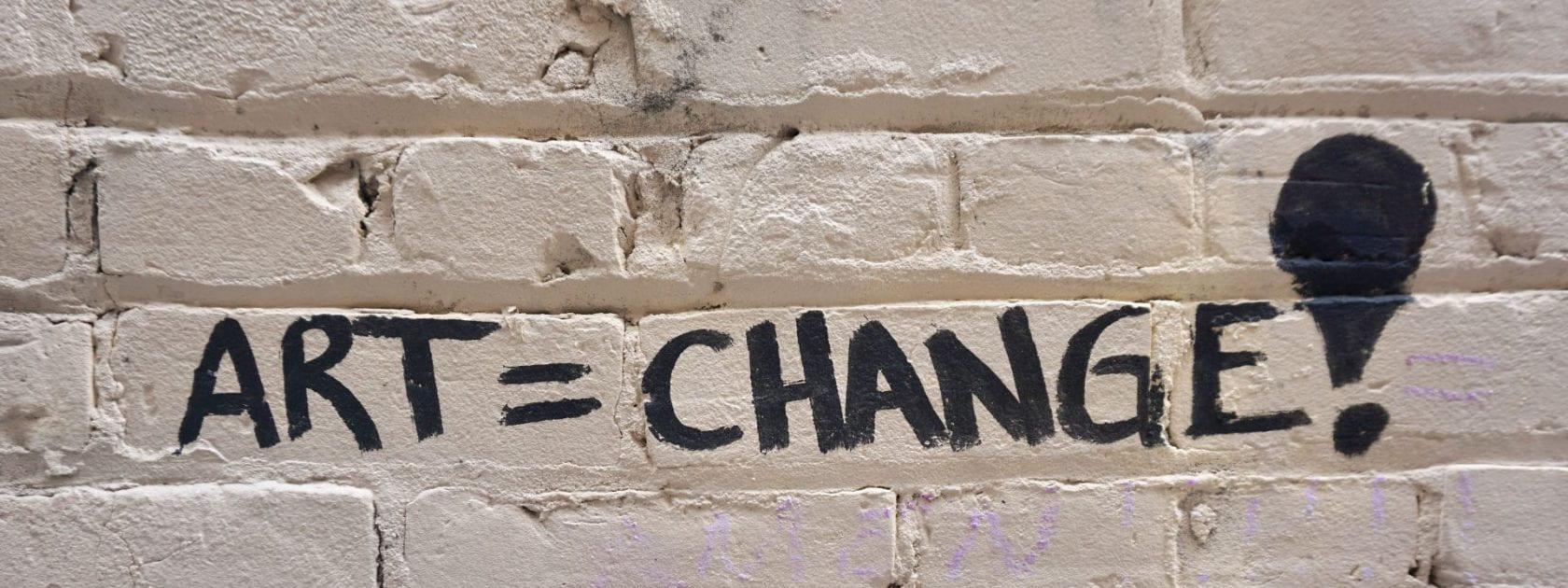 Graffiti on a brick wall that reads ART=CHANGE!