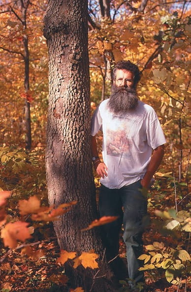 A middle-aged man stands next to a tree in an orange forest. The man has short dark hair and a long grey beard. He is wearing a white t-shirt with a forest graphic on the front and dark jeans.