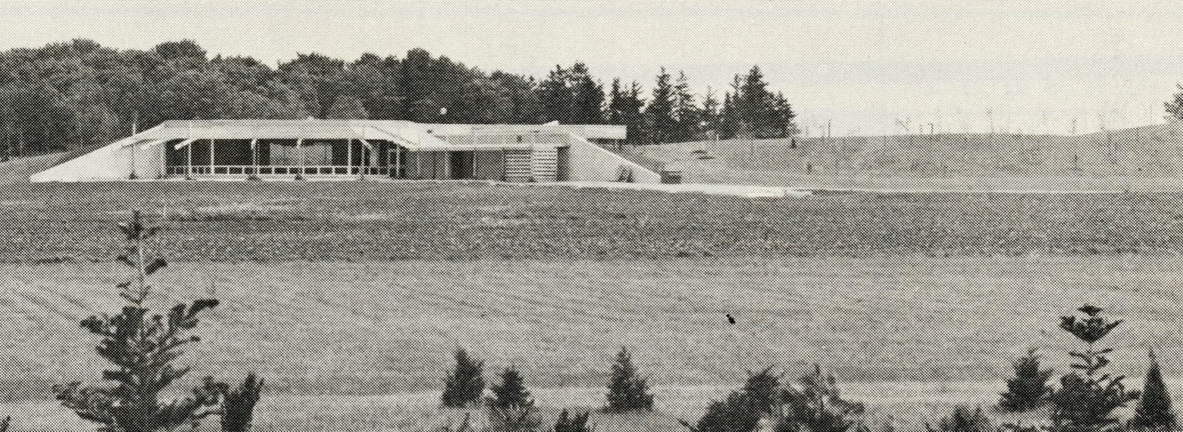 A concrete building with large glass windows sits built into the side of a hill. A large open lawn rests in front of the building. Some small conifer saplings are planted into the lawn at the base of the picture.