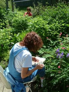 A woman with brown, curly hair sits on a chair facing towards a flower bush with pink and purple blooms. She looks closely at the objects in her hand while she prepares to paint them with a watercolour kit resting on her lap.