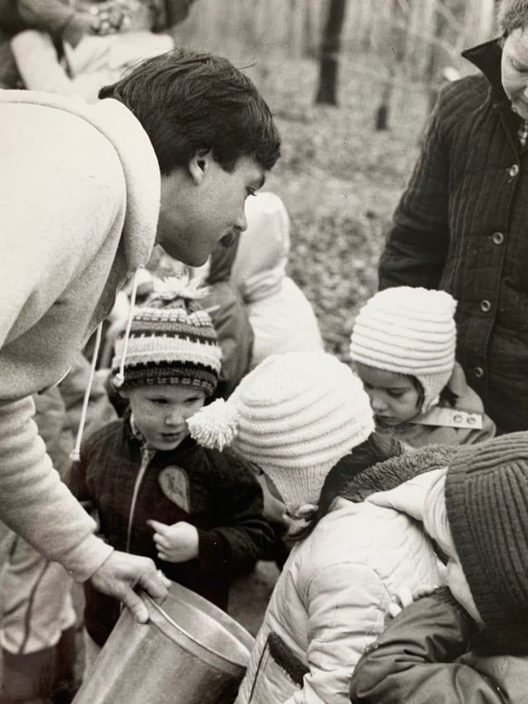 A man with short dark hair leans over, showing the contents of a silver bucket to a group of young children.