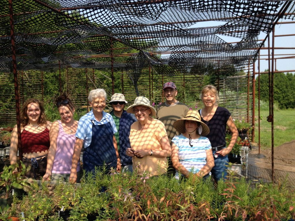 A group of volunteers pose for a picture behind a table of plants.