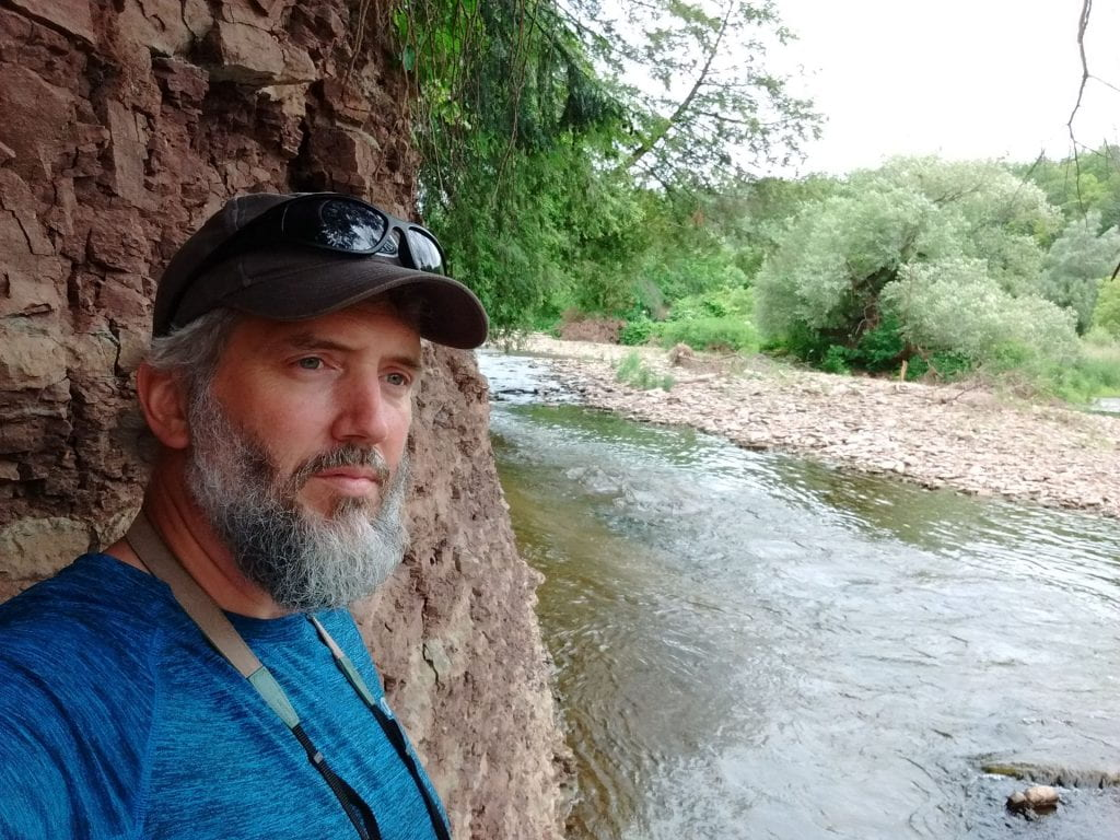 man at the edge of a river with a rock face behind him